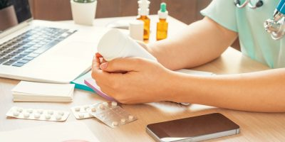 Female medicine doctor filling patient medical form or prescription